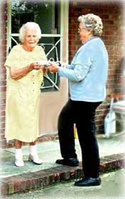 A photograph of a volunteer delivering a meal to a senior at her home.